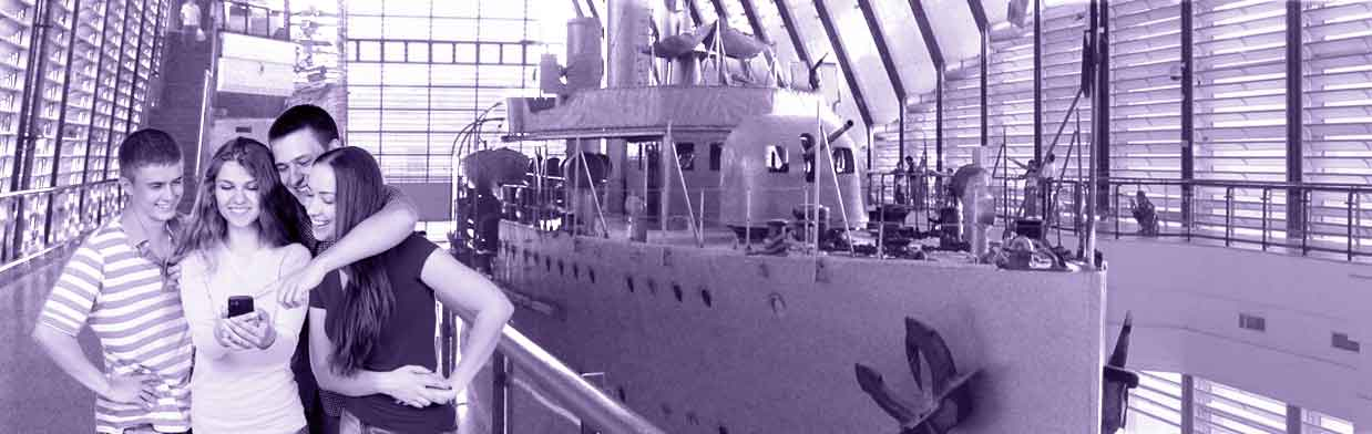 teens engage with a battleship exhibit on their smartphone